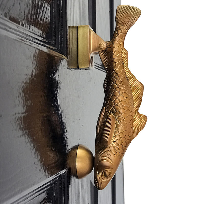 Brass fish door knocker on black door
