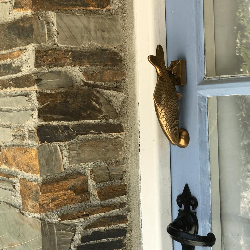 old fish knocker on blue cottage door