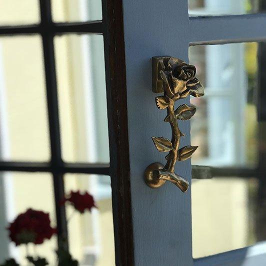rose door knocker on glass paneled door