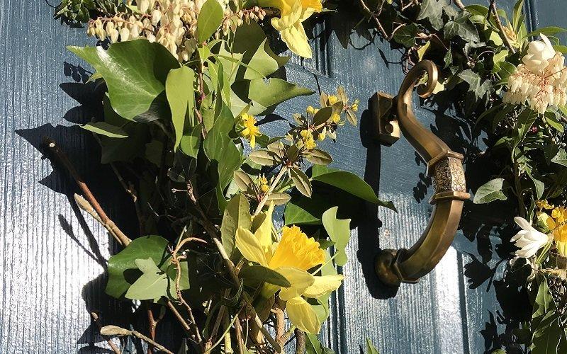 Victorian door knocker on blue front door with spring flowers