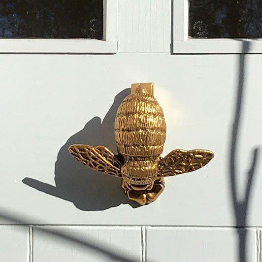 unique brass bee door knocker on white door