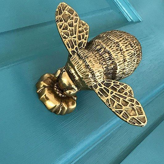 bee door knocker on blue door