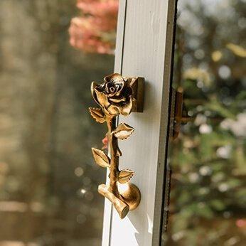 brass rose door knocker on glass door